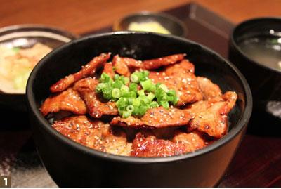 """昼夜の営業問わず、『親子丼』と人気を二分する甘辛な『富士桜ポーク丼』。「はじめて『富士桜ポーク』を試食した際、""""肉質""""以上にそのサラサラとしたベトつかない""""脂""""の旨さに驚いた」という。山梨県の畜産試験場が作り上げた『富士桜ポーク』は、生産量が少ないことからそのほとんどが山梨県内で消費されてしまう銘柄豚だ。店では、甲州地鶏と共に現地から直接仕入れている。"""