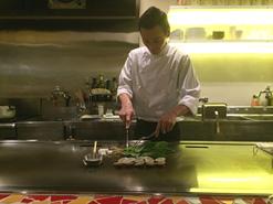 (写真2)鉄板の前でていねいな仕事を見せてくれるオーナーシェフの高 義治さん
