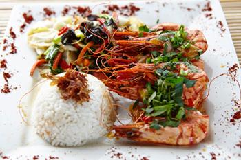 地元の漁師から毎朝新鮮なエビを仕入れて作る「キングプラウン・アラ・バレ ベジタブル&ライス」(95,000 ルピア=約950円)。収益は病院事業に使われる