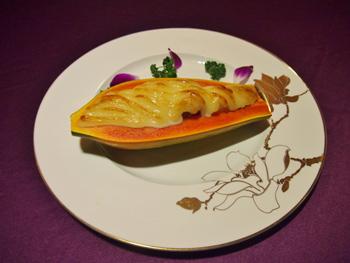 看板メニューのパパイヤ海鮮グラタン「海鮮焗木瓜」。パパイヤをそのまま器として使う盛り付けのアイデアもユニーク