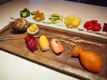 フルーツの握り寿司のネタは左から栗、洛神、柿、ピンクグレープフルーツ、タマリロ。付け合せの漬物は左から順に胡瓜、スターフルーツ、青マンゴー、冬瓜、ミニトマト