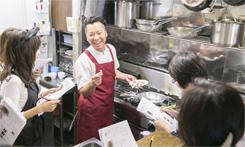 参加者を厨房に招き入れ、間近で調理工程をていねいに説明する山田氏。調理の手順やコツなどをしっかりとレッスンする