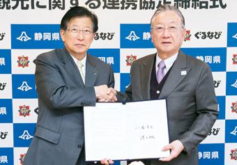 締結式で固い握手を交わす川勝静岡県知事(左)とぐるなび代表取締役会長・創業者 滝