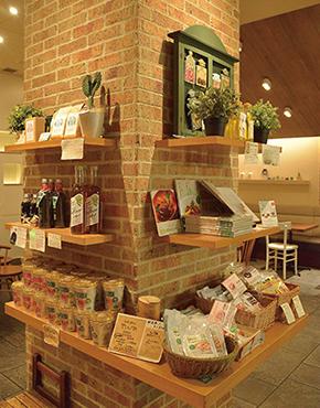 入口のドアのすぐそば、かつ店舗の中央に展開する物販コーナー。店で使っているオリーブオイルやコーヒー豆なども販売している