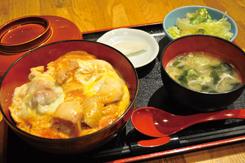 「親子丼並盛」(980円)。比内地鶏の正肉70gを、自家製の割下で煮て、奥久慈卵2個を流し入れ、とろりとした半熟状態に仕上げる。鶏肉の凝縮した旨味と歯応え、濃厚な卵の味わいが、シンプルながら絶妙なハーモニーを生み出している。ミニサラダ、味噌汁、漬物つき
