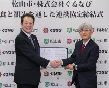 「食と観光を通した連携協定」が締結され、松山市長の野志氏とぐるなびの久保が堅く握手