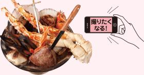 皿からはみ出るズワイガニ、ホタテ、ムール貝などの海鮮に、シズル感のある塊肉(写真は「牛赤身ランプ肉の塊ロースト250g」)もオン!1~2人前のMサイズ(2,786円)もある