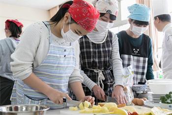 グループに分かれて、エプロン姿で真剣に調理に取り組む子供たち。自然に作業の分担もできていた