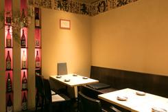テーブル席の壁には日本酒の瓶をディスプレイ。店の売りをアピールしている
