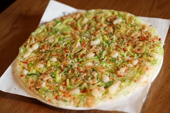 ズッキーニとポテト、エビなどの具材を、溶いた小麦粉と一緒に焼いた「ホガンチジミ」。マッコリと合うメニューとして人気が高い