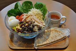 最近人気上昇中の機能性サラダの1品で、「高タンパク&低糖質サラダ」(R1,200円、税込み)。蒸し鶏、スモークサーモン、ゆで玉子、豆類、キノコ類などを使用。おすすめのドレッシングはバルサミコとスイートバジルのミックス。サラダ全品に全粒粉のピタパンがつく。「本日のスープ」(単品350円、サラダとのセット+200円)はミネストローネ