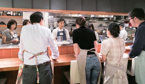 参加者にレッスンメニューについて説明する小倉氏。厨房にメンバーを招き、実践しながら調理指導を行う