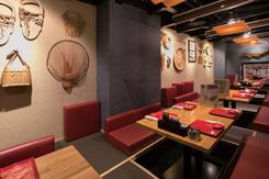クッションやテーブルに置かれた鮮やかな赤の取り皿が映える店内