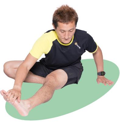 伸ばした脚先の外側を手で押さえ、脚を内側へねじるようにします。