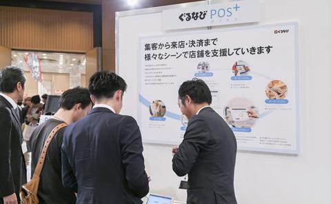 「ぐるなびPOS+(ポスタス)」の展示ブース。飲食店の様々な業務をサポートする新たなサービスに来場者も興味津々