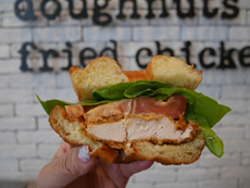 フライドチキンや野菜を挟んだチキンバーガー風ドーナツ。ハンバーガーのバンズやサンドイッチのパンとは違うイーストドーナツ独特のモチモチ感が新感覚