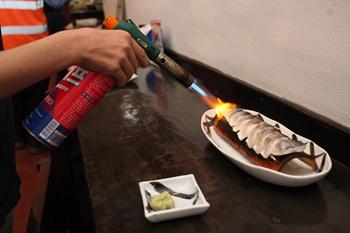 ヒット商品の一つ「焙りしめ鯖」。ラオス人は生の魚には抵抗があると考え、日本の飲食店で提供されるものよりもしっかりと火を通す。仕込みで火を通しておき、仕上げに客の前で豪快にバーナーを使う趣向も好評だ