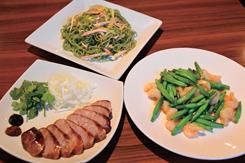 (写真手前左から右回りに)夜のメニューの皮がパリッと香ばしい「自家製 腸詰」(850円)、マレーシア産の金芯菜(きんしんさい/ユリ科のキスゲの仲間のつぼみ)を使った「金芯菜とエビの炒め」(1,250円)、独特のクロレラ麺を使った和え麺の「里麺」(850円)