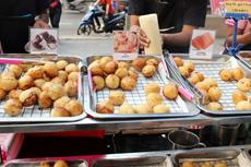 タイの屋台では、「たこ焼き」にタコ以外の具材を使う店も登場。外からは何が入っているかわからないので、ポップに具材の写真を付けている