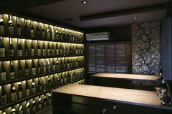 焼酎ボトルが並ぶ2階の壁棚は圧巻のビジュアル。予約は飲み放題付きコース(4,700円~)が7割を占める