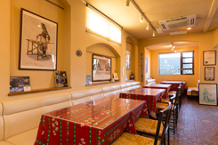 明るい雰囲気のテーブル席。イタリアで購入した絵画やピザに関する本をディスプレイ