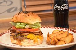 ハンバーガーは22種類(1,050~2,040円)を販売。写真は定番の人気商品「自家製ベーコンチーズバーガー」(1,500円)。アンガス牛の旨みが引き立つパティ、チーズ、5日間かけて作る香ばしい自家製ベーコン、トマト、折りたたんでボリューム感を出したレタスを挟んでいる。ハンバーガーの原価率は40%強と高い