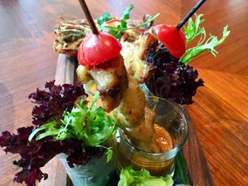 東南アジアで定番の焼き鳥「チキンサテー」は、ピリ辛ソースを入れたグラスの中に立てている。ティースタンドを使わないこともあり、立体感を出した盛り付けが可能になった