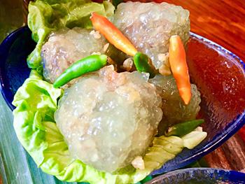 「蒸しサゴ団子」はタイの庶民的おやつ。ヤシの木の幹から採ったでんぷん質「サゴ」で作るほんのり甘い餅で、チリ味の肉団子を包んでいる