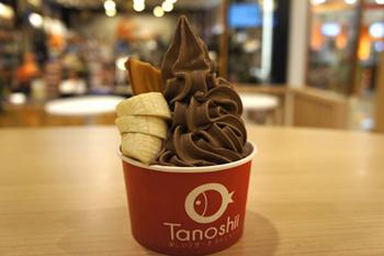 「カップ」で提供する場合は、たい焼きの頭が下になるように立て、ソフトクリームとフルーツが添えられる。写真は、「カスタード×チョコレートソフトクリーム×バナナ」。