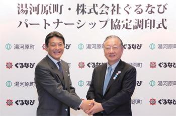 調印式で堅く握手を交わした湯河原町長・冨田幸宏氏(左)と、株式会社ぐるなび代表取締役会長CEO・創業者の滝久雄