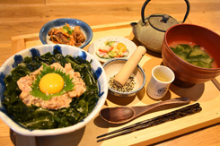 「なめろう丼」(単品680円)の定食(プラス300円)。まずは南高梅の食前酢(手前右から2番目)をひと口飲んで食欲を増進させ、ゴマをすって丼ぶりにかけ、途中まで食べた後、鉄瓶に入った出汁をかけて出汁茶漬けにする。なめろうは、その日に獲れた魚介類を、今川家秘伝のゴマだれで和えた漁師料理。日替わりの小鉢と三浦野菜の漬物が付く