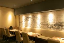 壁面のタイルに波のプリントを施したテーブル席。ほかにカウンターや個室も完備