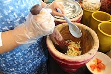 """ソムタムの""""ソム""""は「酸っぱい」、""""タム""""は「(杵などで)つく」という意味。臼の中に具材を入れて、杵でついて具材を柔らかくしながら、混ぜ合わせる"""