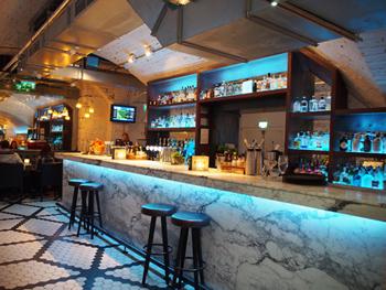 店の入口近くに本格的なスタンディングバーがある。クラフトジンを中心に、生ビール、ワインと多種多様のドリンクを備えており、食事を摂らずサクッと一杯飲んで帰る客もいる