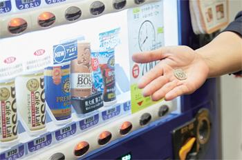料金を投入し、ボタンを押して弁当を注文。釣銭口から購買証明コインが出てくる仕組みで、コインには注文確認と同自販機での飲料10円引きの役割がある