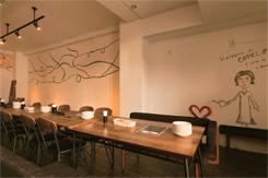 吹き抜けの1・2階からなる店内。壁のイラストでカジュアルな雰囲気を演出