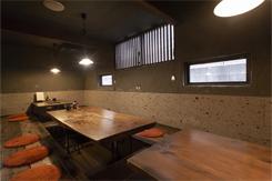 漆喰と大谷石の壁、木目が生きたテーブルが独特の空気感を放つ掘りごたつ席
