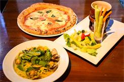 夜の人気メニューから、前菜の「色々野菜のバーニャカウダ」(1296円/写真右)、トマト、モッツァレラ、バジリコのピッツァ「マルゲリータ」(1404円/同上)、アサリ、カラスミ、ホウレン草入りガーリック風味のスパゲッティ「ヴォンゴレビアンコ」(1512円/同左)。3人のイタリア人シェフに師事してきた岡田氏は、味付けやニュアンスなどを若干アレンジし、日本人にとって食べやすいイタリア料理に仕上げている