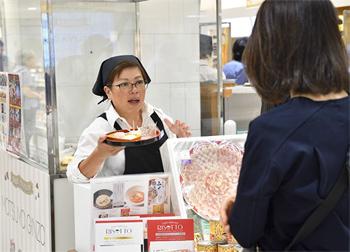 試食をすすめるスタッフ。味を確かめて購入する人も多かった