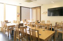 開放的な1階のテーブル席。ほかにカウンターや個室があり、2階には大規模な宴会が可能な座敷席も備える